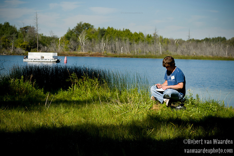 A young man draws a picture by a lake in Ontario, Canada