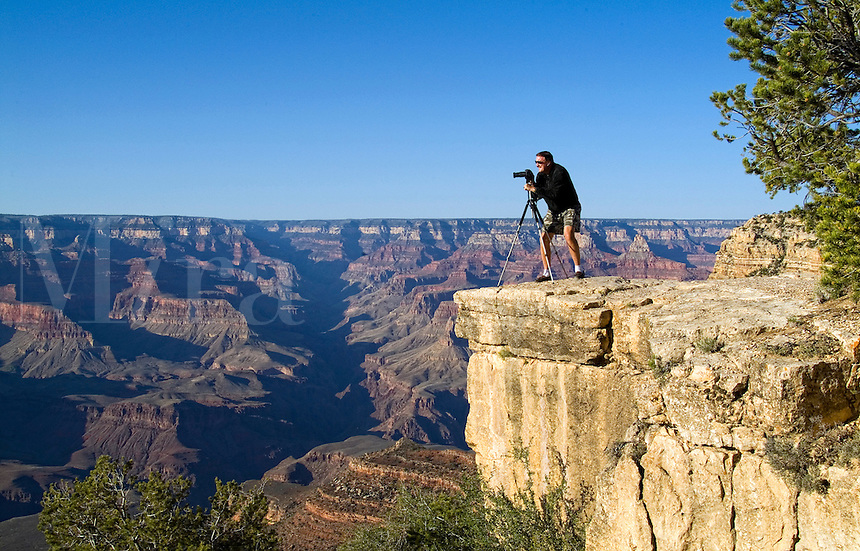 Adventurous photographer taking pictures perched high on cliff at the South Rim, Grand Canyon, Arizona, USA