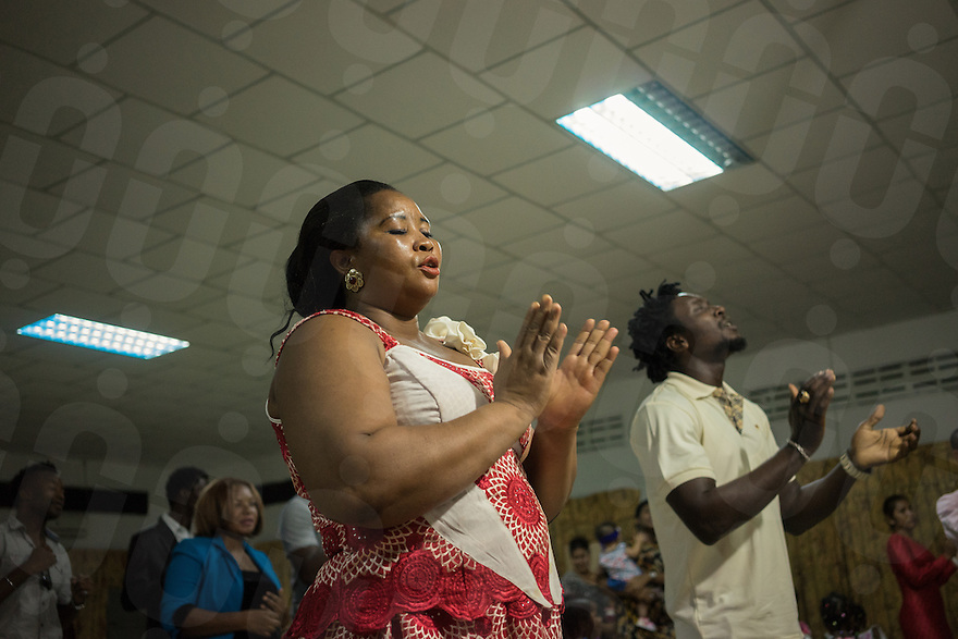 April 06, 2014 - Phnom Penh. Two members of the Christ Embassy Church sing during the Sunday's mass. The Pastor of the church, Prince Lenee Lahben, is known in the Nigerian expat community for his sermons during which he allegedly performs miracles and heals church-goers. © Thomas Cristofoletti / Ruom