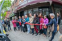 Owner Steve Stiles, with scissors, joined by elected officials and community leaders, at the ribbon cutting for the newly reopened Stile's Farmers Market in the Hell's Kitchen neighborhood of New York on Sunday, May 7, 2017. After being forced out from their original location, where it had been tor over 20 years, almost three years ago because the building was sold and developed the popular market, known for its affordability and quality produce, has reopened a few blocks down from its original location on Ninth Avenue. (© Richard B. Levine)