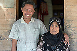Idris Zendrato and his wife in the village of Moawo on the Indonesian island of Nias. He helped plant mangrove seedlings along the nearby coastline following a devastating 2004 tsunami and 2005 earthquake. The mangrove planting was part of assistance provided to the village by YEU, a member of the ACT Alliance. Their family's house was flattened by the waves, and after months of living in temporary shelters on nearby hillsides, the family moved into one of 72 new homes constructed in the village by YEU. With foundations of cement, they are more resilient than the pre-tsunami houses which were built entirely of wood. YEU also helped the community members restart their local economy, including the replanting of mangroves to protect the shoreline and revitalize their fishing industry.