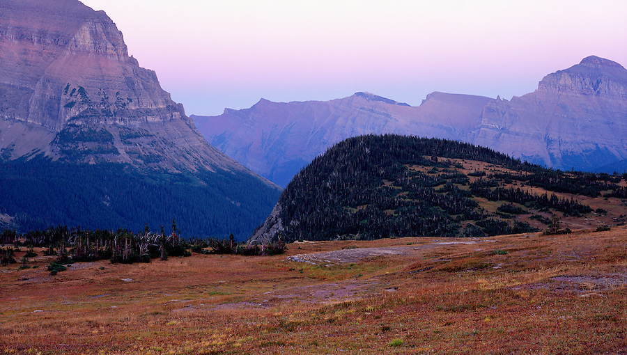 Twilight casts purplish light on the peaks visible from Logan Pass in Glacier National Park, Montana.