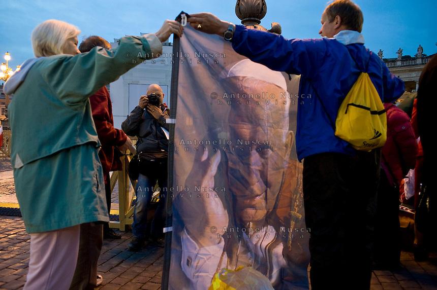 Faithful holding Pope banner in Saint Peter Square before the Beatification ceremony for Pope John Paul II..Fedeli mostrano una immagine di Giovanni Paolo secondo in Piazza San Pietro prima della sua Beatificazione.