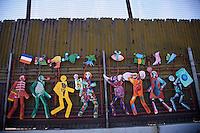 Confine Arizona Messico Nogales , il muro che divide Stati Uniti e Messico decorato con figure ch esimbioleggiano i migranti nel tentativo di attraversare il deserto