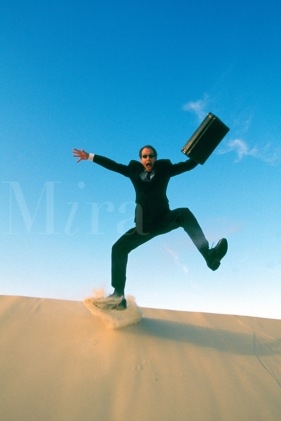 Australia, Qld., businessman leaping off sand dune.  MR available.