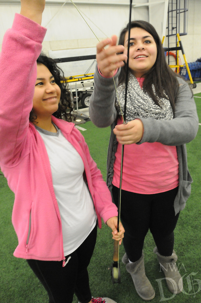 NWA Democrat-Gazette/FLIP PUTTHOFF<br /> FLY CASTING<br /> Estefani Corleto (left) and Stephanie Rodriguez, seniors at Rogers High School, assemble a fly-fishing rod during a  casting lesson Tuesday Jan. 19, 2016 in outdoor education class. Outdoor ed students are learning to fly fish as part of their preparation for a trout fishing trip to Roaring River State Park near Seligman, Mo., later this semester. Students learn to tie knots, tie flies and study aquatic life as part of the fly fishing unit.