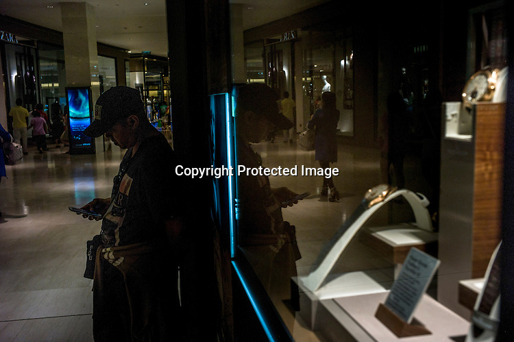 A shopper stops to check his mobile phone at the Pavilion, a high end shopping mall in Kuala Lumpur, Malaysia.