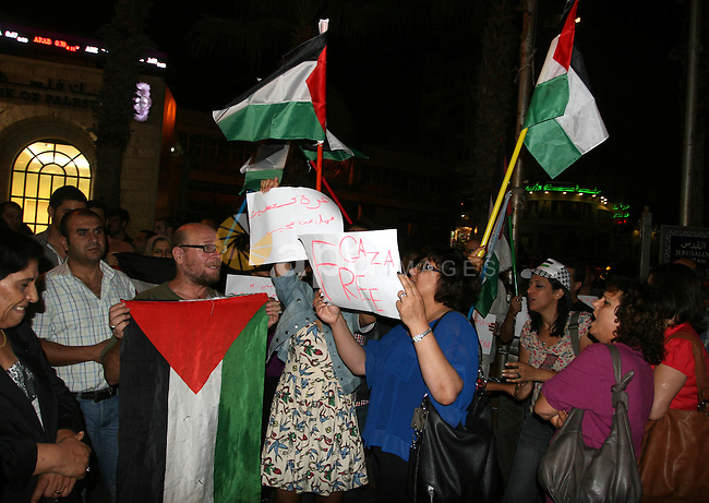 Palestinians wave with their national flag and hold placards during a protest in solidarity with the people in Gaza Strip, in the West Bank city of Ramallah on August 19,2011. Israel struck Gaza with two days of air strikes killing ten militants and two civilians, children aged 2 and 13. Photo by Issam Rimawi