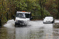 Pictured: A tipper lorry drives past a Vauxhall Astra convertible which is stranded on the B4242 road between Resolven and Glyn Neath in south Wales, UK. Saturday 13 October 2018<br /> Re: Flooding caused by Storm Callum in the Neath area, south Wales, UK.
