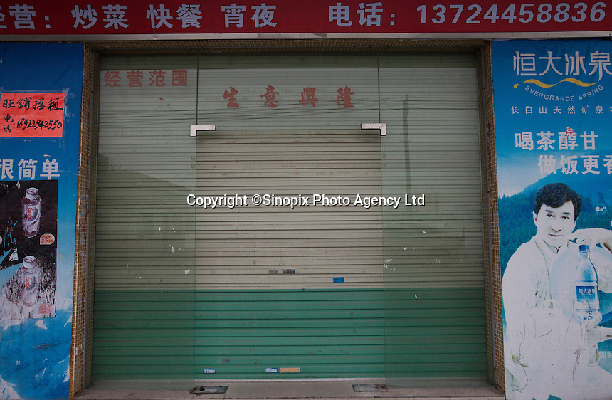 A shutttered shop is seen near the Yue Yuen Industrial Holdings Limited factory in Dongguan, Guangdong Province, China, 03 March 2015.