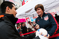 former women's national team player April Heinrichs autographs a ball for a fan during the centennial celebration of U. S. Soccer at Times Square in New York, NY, on April 04, 2013.