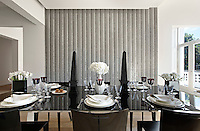 A fluted mirror mosaic feature wall is the unusual backdrop in a contemporary dining room. A polished black lacquer table is set for dinner.
