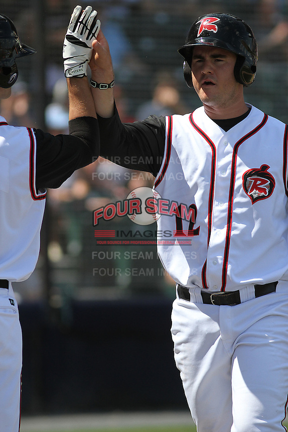 """Richmond Flying Squirrels first baseman Tommy Joseph #12 """"high fiving"""" a teammate after scoring a run during a game against the Trenton Thunder at The Diamond on May 27, 2012 in Richmond, Virginia. Richmond defeated Trenton by the score of 5-2. (Robert Gurganus/Four Seam Images)"""