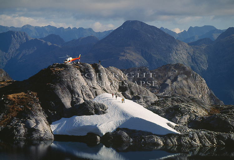 Squirrel helicopter on snow with tourists in the Kepler Mountains Fiordland National Park New Zealand