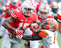 Ohio State Buckeyes running back Ezekiel Elliott (15) runs over Florida A&M Rattlers linebacker George Maxey (6) in the 4th quarter during their college football game at Ohio Stadium on September 21, 2013.  (Dispatch photo by Kyle Robertson)