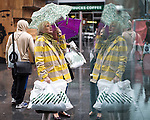 © Joel Goodman - 07973 332324 . 26/09/2016 . Liverpool , UK . Shoppers and tourists at Liverpool One shopping centre shelter under umbrellas as blustery showers end a spell of warm sunshine . Photo credit : Joel Goodman