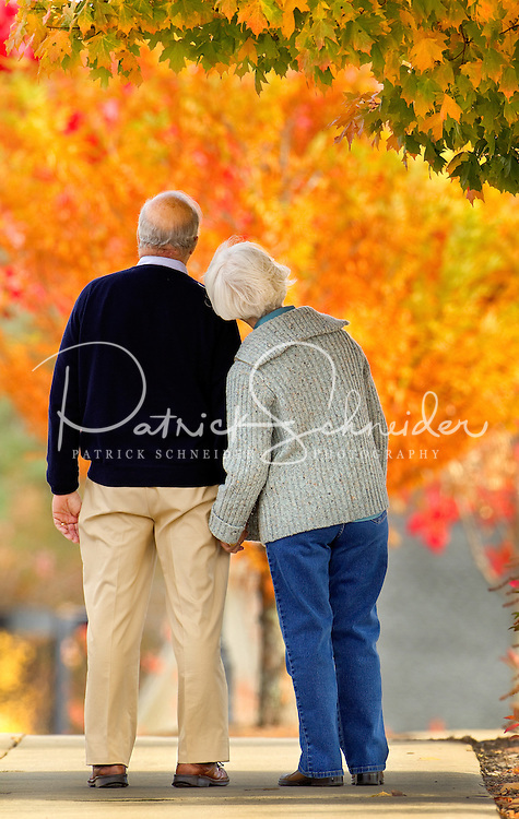 A couple holds hands against a backdrop of colorful autumn leaves in Asheville NC's Biltmore Park Town Square, a planned community in the Blue Ridge Mountains of residential living, office spaces and shopping.