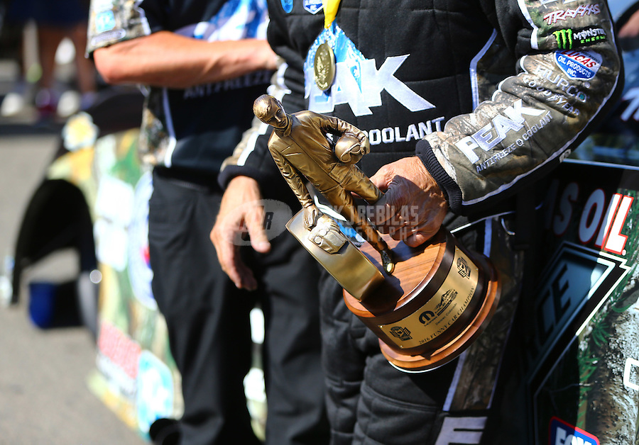 Jul 24, 2016; Morrison, CO, USA; Detailed view of the Wally trophy in the hand of NHRA funny car driver John Force as he celebrates after winning the Mile High Nationals at Bandimere Speedway. Mandatory Credit: Mark J. Rebilas-USA TODAY Sports