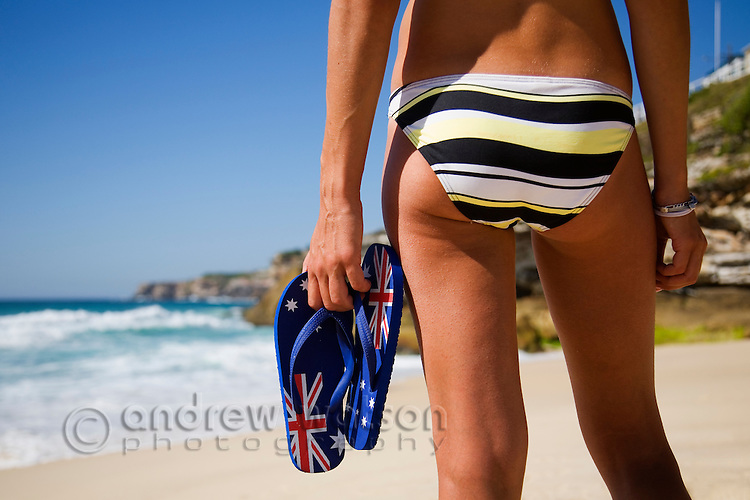 A woman holds a pair of Aussie flip flops at Tamaram on Sydney's eastern beaches.  Sydney, New South Wales, AUSTRALIA.