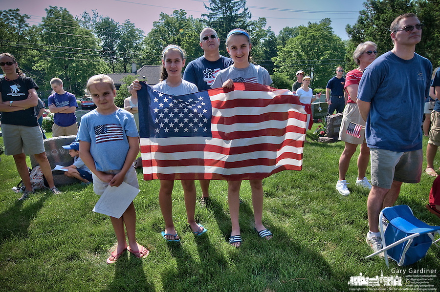 A family displays and American flag during ceremonies for a Memorial Day observance at Otterbein Cemetery following  the Memorial Day parade through Uptown Westerville