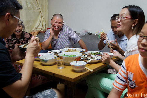 Former farmers dine in southern China in their newly furnished apartment given by the government in return for seized land.<br /> <br /> China is pushing ahead with a dramatic, history-making plan to move 100 million rural residents into towns and cities over six years &mdash; but without a clear idea of how to pay for the gargantuan undertaking or whether the farmers involved want to move.<br /> <br /> Moving farmers to urban areas is touted as a way of changing China&rsquo;s economic structure, with growth based on domestic demand for products instead of exporting them. In theory, new urbanites mean vast new opportunities for construction firms, public transportation, utilities and appliance makers, and a break from the cycle of farmers consuming only what they produce.<br /> <br /> Urbanization has already proven to be one of the most wrenching changes in China&rsquo;s 35 years of economic reforms. Land disputes rising from urbanization account for tens of thousands of protests each year.