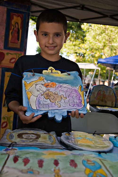Youth artist,Marcos Valenzuela, holds his hand painted wooden retablos at the Santa Fe Indian Market