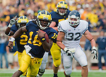 Michigan quarterback Denard Robinson (16) rushes past Connecticut linebacker Scott Lutrus (32) on the carry, in the first quarter of an NCAA college football game, Saturday, Sept. 4, 2010, in Ann Arbor, Mich. (AP Photo/Tony Ding)