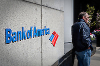 A man smokes a cigarette by the a Bank of America logo in Toronto financial district April 22, 2010. Bank of America Corporation (NYSE: BAC) is a financial services company, the largest bank holding company in the United States, by assets, and the second largest bank by market capitalization.