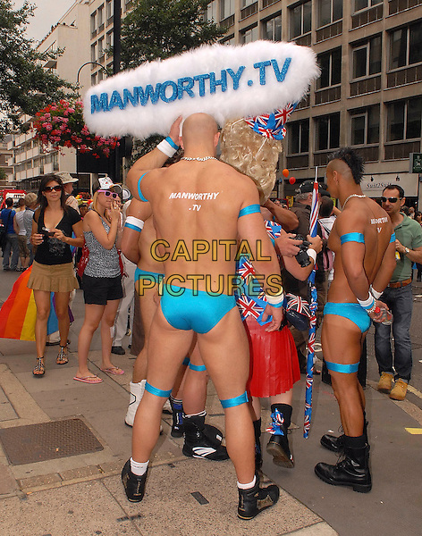 ATMOSPHERE .The UK's largest gay and lesbian festival, Gay Pride, parades through central London. This years parade theme is entitled 'Come Out and Play..July 4th, 2009.march full length gv general view costume blue speedo back behind rear manworthy.com white sign.CAP/IA.©Ian Allis/Capital Pictures.