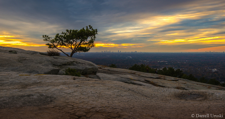 Scenic landscape photograph of Stone Mountain near Atlanta Georgia. A beautiful sunset, shining golden rays to create a surreal moon like view of Stone Mountain, with the City of Atlanta in the distant horizon.