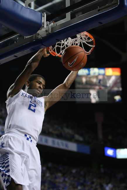 Kentucky guard Aaron Harrison swings on the rim after dunking the ball during the first half of the UK men's basketball exhibition game against Georgetown College at Rupp Arena on Sunday, November 9, 2014 in Lexington, Ky. Kentucky leads Georgetown 60 to 24. Photo by Adam Pennavaria | Staff