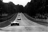 LE MANS, FRANCE - JUNE 16: A group of cars exits the Mulsanne Corner during the 24 Hours of Le Mans FIA World Sports Car Championship race at Circuit de la Sarthe near Le Mans, France, on June 16, 1985.