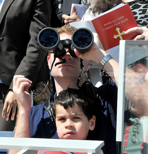 Washington, DC - April 17, 2008 -- Ronan Sorensen of North Bethesda, Maryland watches with his binoculars as Pope Benedict XVI celebrates Mass at the new Nationals Park in Washington, D.C. on Thursday, April 17, 2008. This is the first non-baseball event in the park, which opened March 31.  His son, Christian is on his lap..Credit: Ron Sachs / CNP.(RESTRICTION: NO New York or New Jersey Newspapers or newspapers within a 75 mile radius of New York City)