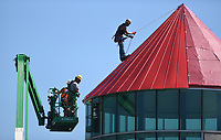 Levi Roper (from left), Levi Clay and Jarrid Giese, all with Daniel Cowin Construction, replace Wednesday, June 24, 2020, the metal roof on the high point of the Donald W. Reynolds Boys & Girls Club in Fayetteville. The roof had been damaged by a storm. Check out nwaonline.com/200625Daily/ and nwadg.com/photos for a photo gallery.<br /> (NWA Democrat-Gazette/David Gottschalk)