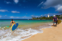 After standup paddling in Waimea River, a woman and man look out over Waimea Bay at Waimea Beach Park, O'ahu.
