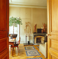 In the salon Tibetan rugs adorn the parquet floor and a pair of carved wooden figures is displayed on the original 18th century marble fireplace