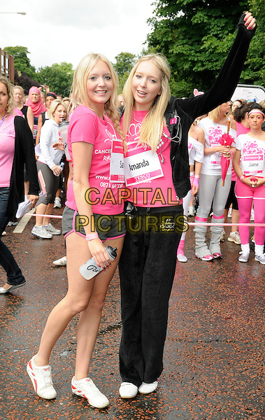 SAMANDA - SAMANTHA & AMANDA MARCHANT.Cancer Research Race For Life Charity 5k Run at Hyde Park, London, England. .July 19th 2009 .full length sam twins sisters siblings family pink t-shirt black shorts tracksuit drink water bottle braid plait trainers sneakers arm in air .CAP/CAN.©Can Nguyen/Capital Pictures.