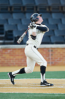 Conor Keniry (14) of the Wake Forest Demon Deacons follows through on his swing against the Towson Tigers at Wake Forest Baseball Park on February 15, 2014 in Winston-Salem, North Carolina.  The Tigers defeated the Demon Deacons 5-4.  (Brian Westerholt/Four Seam Images)