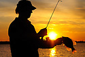 00247-012.02 Black Crappie: Angler is silhouetted against low sun as he displays large crappie.  Spawn, spring, spinning..