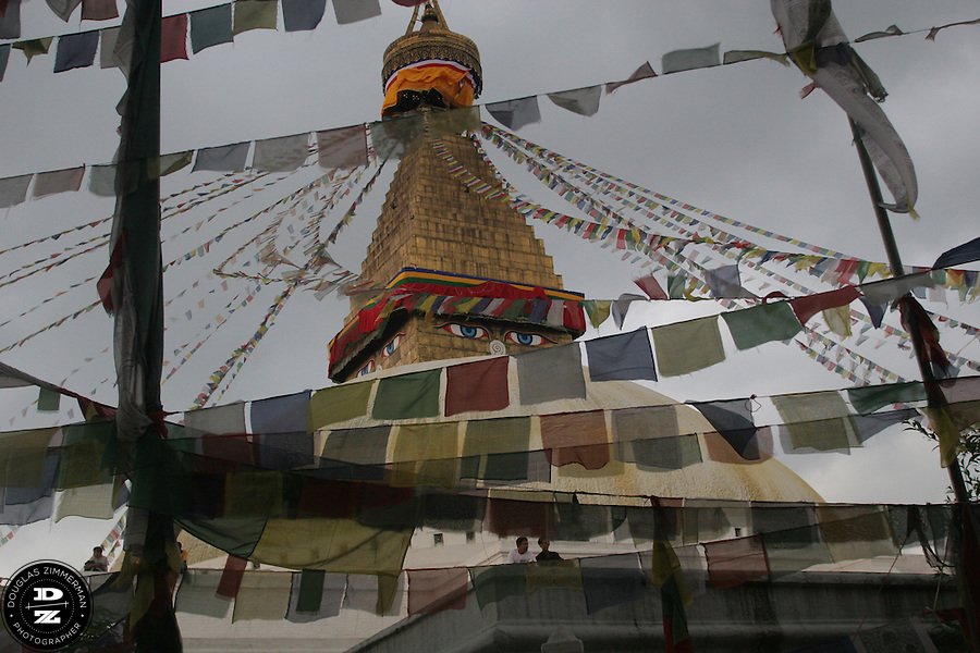 Prayer flags blow in the wind as they hang from and around the stupa at Boudha (or Boudhanath) just outside Kathmandu, Nepal.  The stupa is considered the most important Tibetan Buddhist monument outside Tibet.  Photograph by Douglas ZImmerman