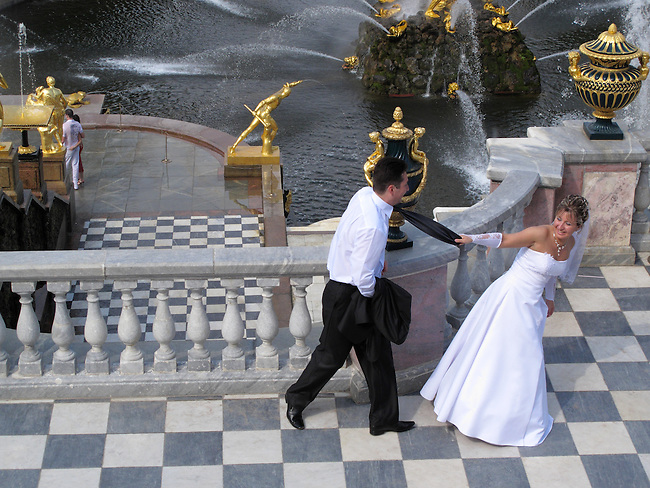 Wedding couple, with gilded fountains and the Great Canal behind. Peterhof Palace. Near St. Petersburg, Russia.