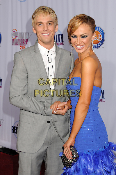 AARON CARTER & KARINA SMIRNOFF.2009 Fox Reality Channel Really Awards held at the Music Box Theatre, Hollywood, California, USA..October 13th, 2009.half length blue strapless drop waist feather holding hands grey gray suit jacket dress silver clutch bag.CAP/ADM/BP.©Byron Purvis/AdMedia/Capital Pictures.