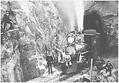 A mostly frontal view of D&amp;RG American #100 and her crew posing at the west portal of Rock Tunnel.<br /> D&amp;RG  Rock Tunnel, NM  Taken by Jackson, William Henry