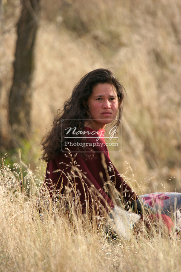 A young Native American Indian woman sitting in the tall grass of South Dakota looking upset and sad