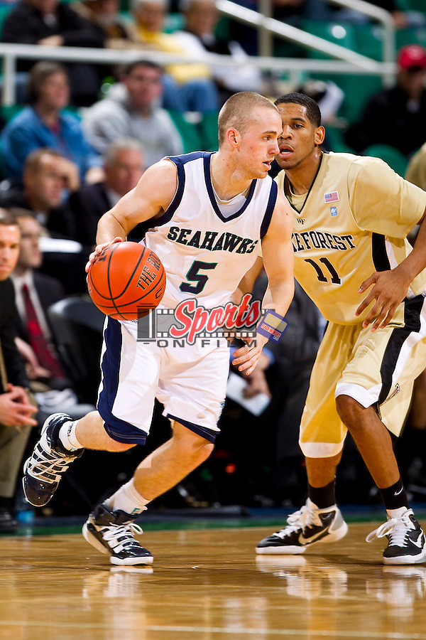 Chad Tomko #5 of the UNC-Wilmington Seahawks dribbles the ball as C.J. Harris #11 of the Wake Forest Demon Deacons defends at the Greensboro Coliseum on December 12, 2010 in Greensboro, North Carolina.  The Seahawks defeated the Demon Deacons 81-69. Photo by Brian Westerholt / Sports On Film
