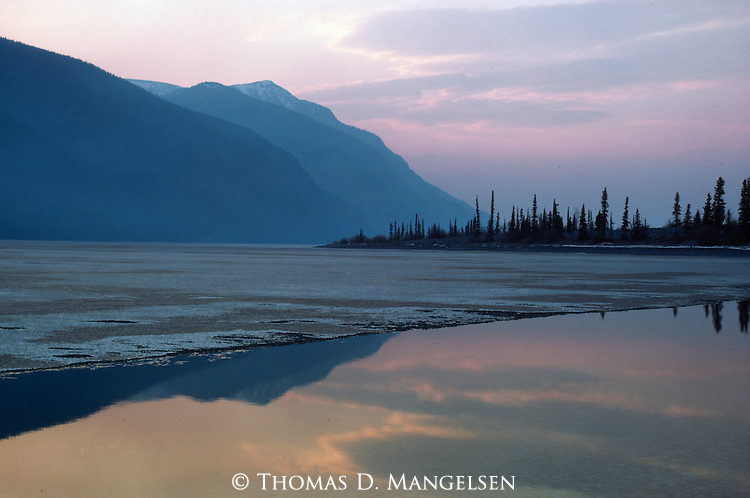 The colors of sunset reflect on the water of Yukon Lake exposed by the ice that has receded with the coming of spring in Yukon, Canada.