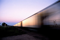 A freight train races through the countryside, alongside US 30, Indiana, USA