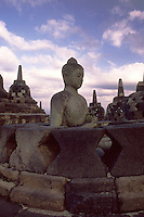 Central Java, Indonesia: detail of The Borobudur temple, Buddha statue surrounded by stupas.<br /> Indonesia, Giava: dettagli del tempio Borobudur, Statua del Buddha attorniata dalle stupe.