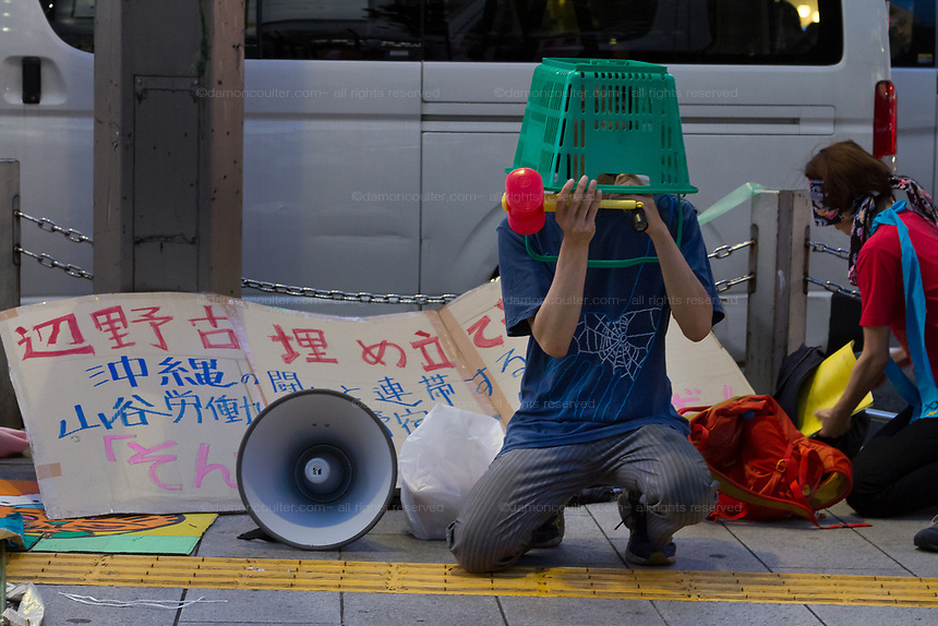 A younger Japanese man wearing a shopping basket on his head at a small protest against the staging of the Olympic Games in Shinjuku, Tokyo, Japan Friday June 30th 2017. Though mostly popular with the Japanese population he staging of the 2020 Olympic Games in Tokyo is felt by some to be a waste of money when the economy is bad, causing increasing poverty rates and with problems in the Tsunami damaged North East coast still not fully resolved.