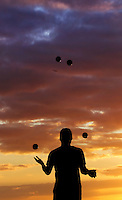 A man juggles balls while silhouetted against a colorful sky at sunset, Hawai'i.